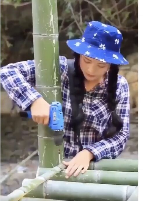 Young Woman Single-handedly Building House of Bamboo